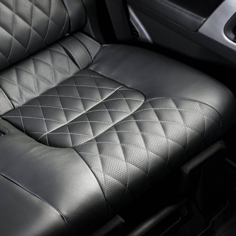 Back passenger seats in modern luxury car, frontal view, black perforated leather with stitching