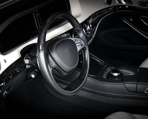 Modern luxury prestige car interior, dashboard, steering wheel. Black and white leather interior. Isolated windows, clipping path included